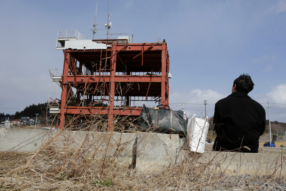 . A man sits in front of what is left of a disaster control center in an area devastated by the March 11, 2011 earthquake and tsunami, in Minamisanriku, Miyagi Prefecture, northern Japan, Tuesday, March 11, 2014. Japan marked the third anniversary on Tuesday of a devastating disasters that left nearly 19,000 people dead or missing. (AP Photo/Shizuo Kambayashi)