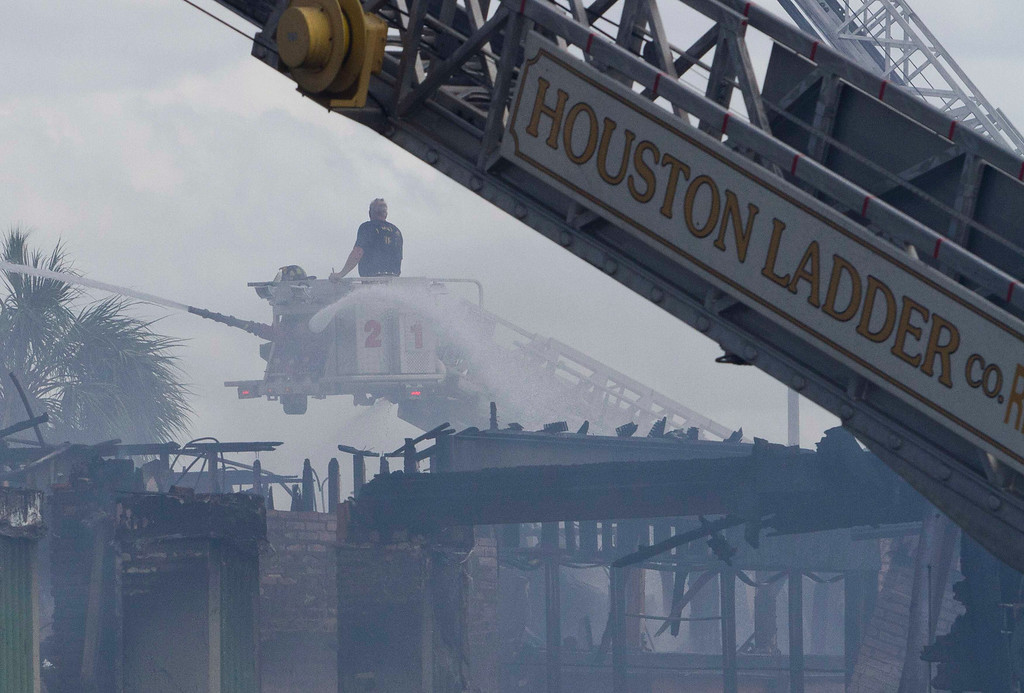 . A ladder truck sprays water on the fire where four firefighters were killed battling a a five-alarm blaze at a restaurant and hotel in southwest Houston May 31, 2013.     REUTERS/Richard Carson