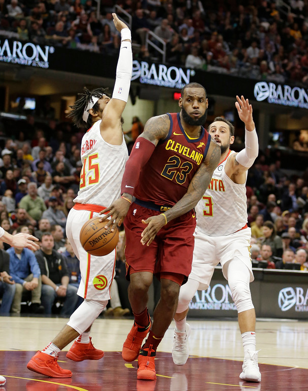 . Cleveland Cavaliers\' LeBron James (23) passes around Atlanta Hawks\' DeAndre\' Bembry (95) and Marco Belinelli (3) in the second half of an NBA basketball game, Tuesday, Dec. 12, 2017, in Cleveland. (AP Photo/Tony Dejak)