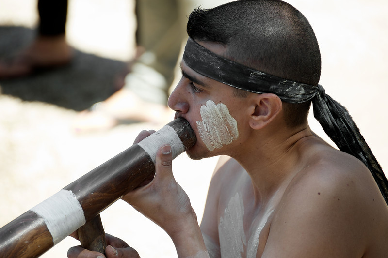 Young Aboriginal Man in Traditional Costume playing Didgeridoo outdoors, on a blurred background