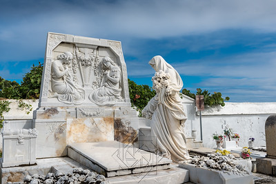 White statue of a women standing near a grave