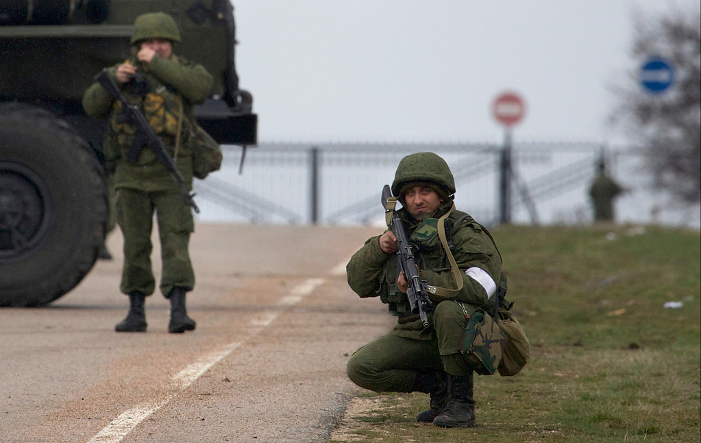 . An unidentified gunman holds his assault rifle ready while he and others block the road toward the military airport at the Black Sea port of Sevastopol in Crimea, Ukraine, Friday, Feb. 28, 2014. (AP Photo/Ivan Sekretarev)