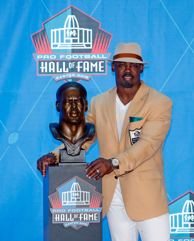 . Former NFL safety Brian Dawkins poses with a bust of himself during inductions at the Pro Football Hall of Fame, Saturday, Aug. 4, 2018 in Canton, Ohio. (AP Photo/Gene J. Puskar)