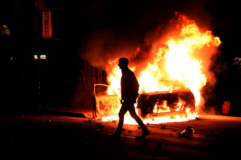 . A man walks past a burning police vehicle during clashes between police and protesters over the decision in the shooting death 18-year-old Michael Brown in Ferguson, Missouri, on November 24, 2014. US President Barack Obama urged calm as violent protests broke out on the streets of Ferguson after a grand jury decided a white policeman will not face charges for killing a black teen. AFP PHOTO/Jewel SAMAD/AFP/Getty Images