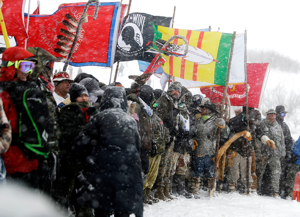 . Military veterans and Native American tribal elders come to a stop for a ceremonial prayer during a march to a closed bridge across from the Dakota Access oil pipeline site in Cannon Ball, N.D., Monday, Dec. 5, 2016. (AP Photo/David Goldman)