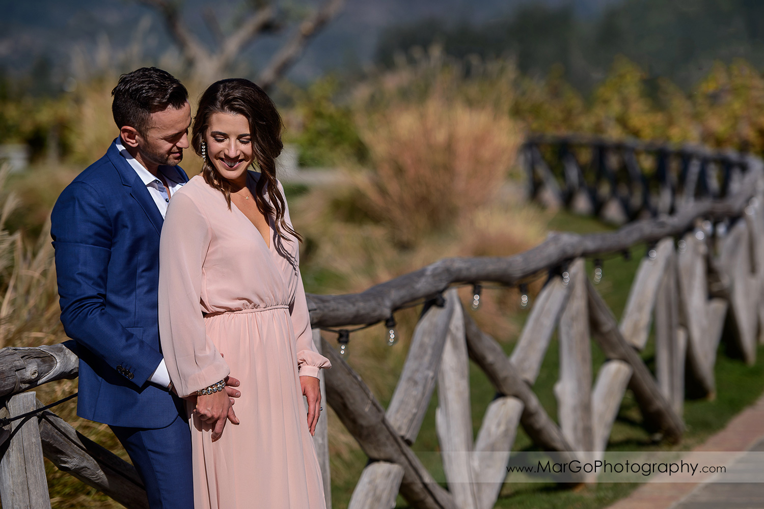 portrait of woman in pink dress and man in blue suit on the wooden fence during Napa Valley engagement session at Castello di Amorosa in Calistoga