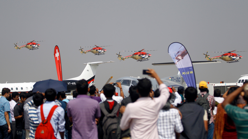 Description of . Visitors watch Indian Air Force helicopters perform an aerobatic flight on the second day of the Aero India 2013 at Yelahanka air base in Bangalore, India, Thursday, Feb. 7, 2013. More than 600 aviation companies along with delegations from 78 countries are participating in the five-day event that started Wednesday. (AP Photo/Aijaz Rahi)