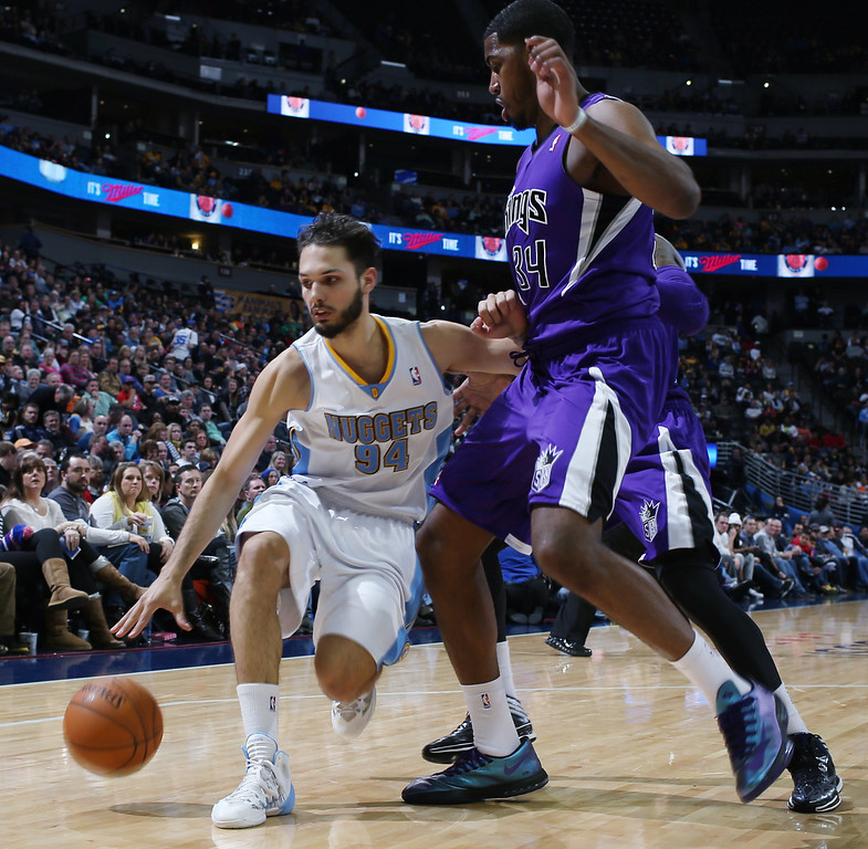 . Denver Nuggets guard Evan Fournier, left, of France, pursues loose ball as Sacramento Kings forward Jason Thompson covers in the fourth quarter of an NBA basketball game in Denver on Sunday, Feb. 23, 2014. The Kings won 109-95. (AP Photo/David Zalubowski)
