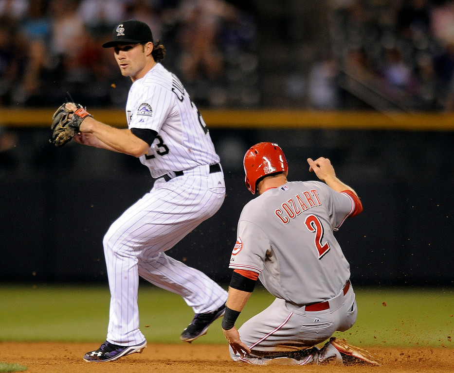 . Colorado Rockies shortstop Charlie Culberson forces out Cincinnati Reds Zack Cozart at second base in the fifth inning of a baseball game Thursday, Aug. 14, 2014, in Denver. Alfredo Simon was safe at first. (AP Photo/Chris Schneider)