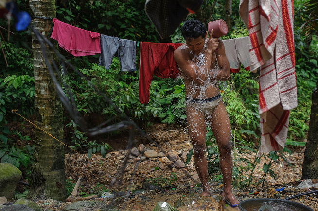 . A miner takes a bucket-shower at the end of a day of digging on April 23, 2014 in Pinut-An, Philippines. The tunnels are wet and muddy, and the miners shower several times a day to stay clean, on April 23, 2014 in Pinut-An, Philippines.  (Photo by Luc Forsyth/Getty Images)
