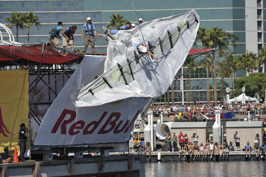 """. LONG BEACH, CALIF. USA -- Flugtag team members throw their entry \""""Flies Like a Butterfly, but Stings Like a Ray\""""after it failed to roll down the ramp in Rainbow Harbor in Long Beach, Calif. on August 21, 2010. Thirty five teams competed in the Red Bull event where teams build homemade, human-powered flying machines and pilot them off a 30-foot high deck in hopes of achieving flight.  Flugtag means \""""flying day\"""" in German. They are on distance, creativity and showmanship..Photo by Jeff Gritchen / Long Beach Press-Telegram.."""