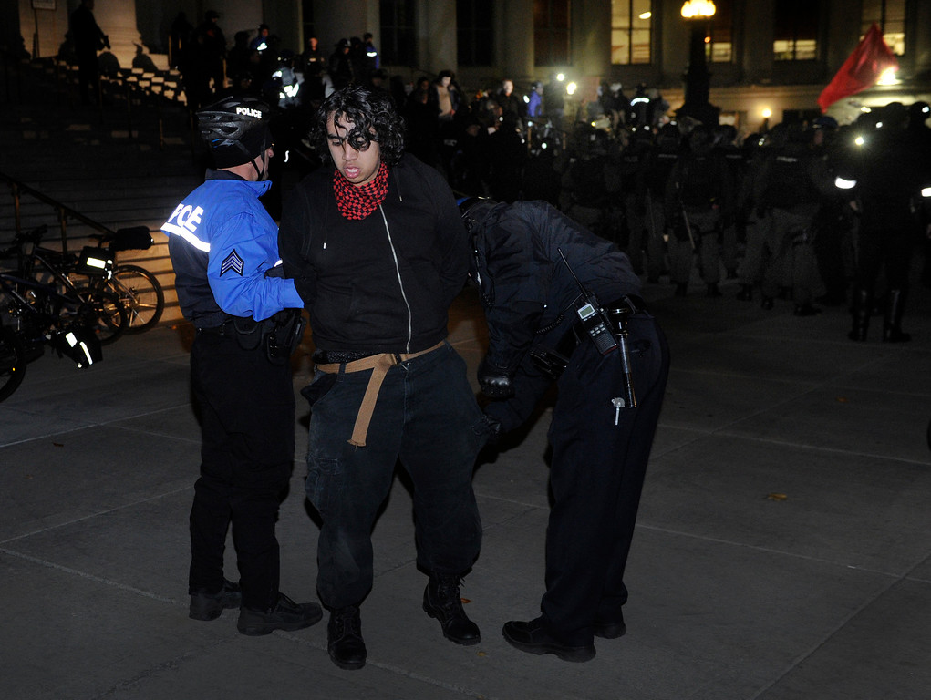 . DENVER, CO. - NOVEMBER 5: Denver Police officers checked the pockets of a protester they accused of using spray paint on the steps of the City and County Building Tuesday night. Two hundred protesters calling themselves Anonymous tied up traffic in downtown Denver Tuesday night, November 5, 2013.  Photo By Karl Gehring/The Denver Post