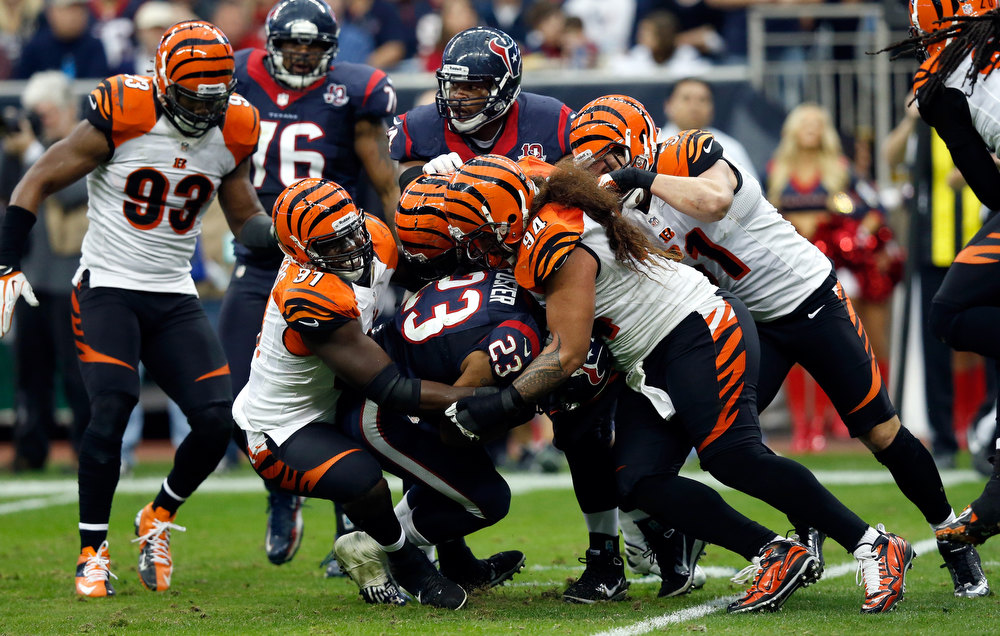 . Arian Foster #23 of the Houston Texans is tackled in the first half by Geno Atkins #97 and Domata Peko #94 of the Cincinnati Bengals during their AFC Wild Card Playoff Game at Reliant Stadium on January 5, 2013 in Houston, Texas.  (Photo by Scott Halleran/Getty Images)