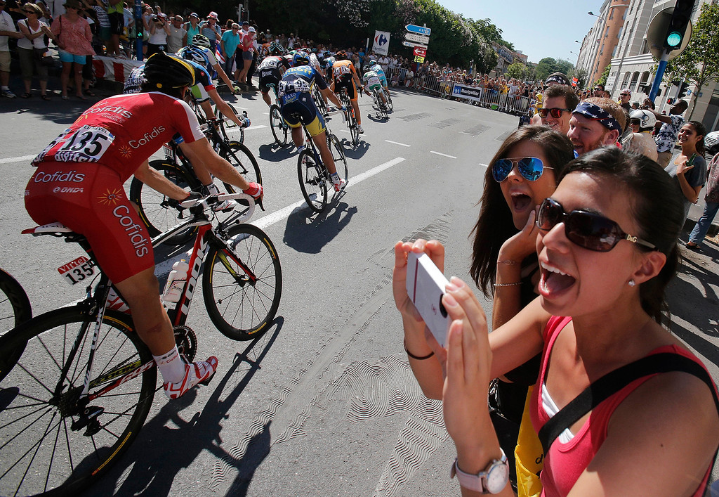 . Spectators cheers as the pack passes during the sixth stage of the Tour de France cycling race over 176.5 kilometers (110.3 miles) with start in Aix-en-Provence and finish in Montpellier, southern France, Thursday July 4, 2013. (AP Photo/Christophe Ena)