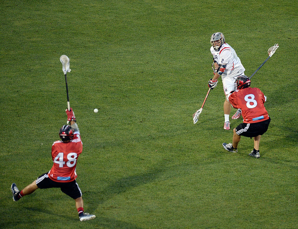 . United States attack Brendan Mundorf (2) fired a shot past Canada defenders Kyle Rubisch (8) and Matt Vinc (48) for a goal in the second quarter. The United States took on Canada in the opening game of the FIL World Lacrosse Championships Thursday night, July 10, 2014.   Photo by Karl Gehring/The Denver Post