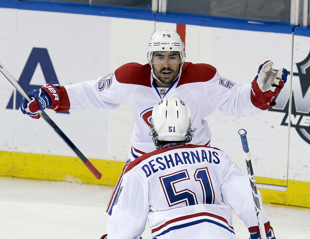 . Montreal Canadiens\' Francis Bouillon, top, celebrates with David Desharnais (51) after scoring during the second period of Game 4 of the NHL hockey Stanley Cup playoffs Eastern Conference finals against the New York Rangers, Sunday, May 25, 2014, in New York. (AP Photo/Seth Wenig)