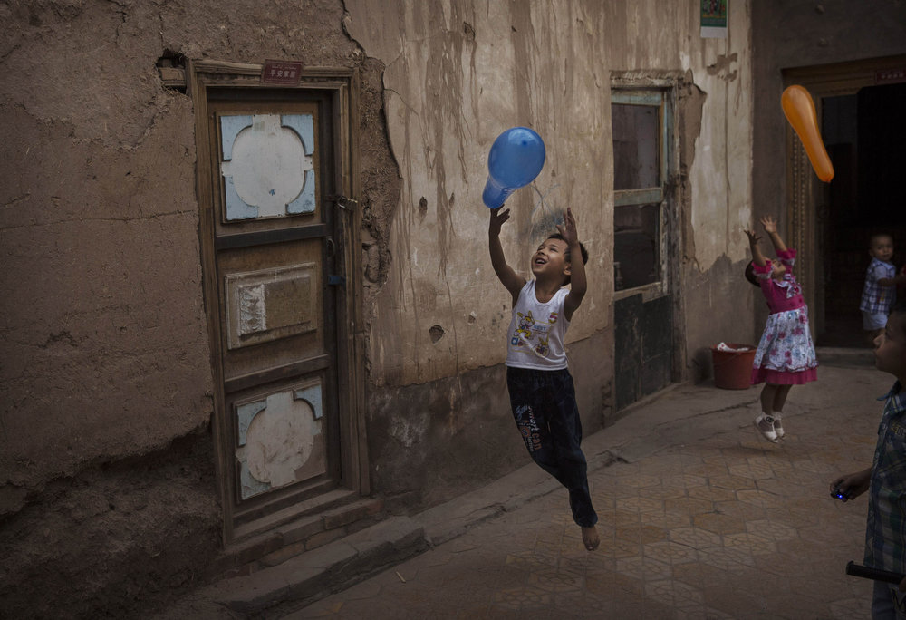 . KASHGAR, CHINA - JULY 29: Uyghur children play with balloons on the Eid holiday on July 29, 2014 in alleyway in old Kashgar, Xinjiang Province, China. Nearly 100 people have been killed in unrest in the restive Xinjiang Province in the last week in what authorities say is terrorism but advocacy groups claim is a result of a government crackdown to silence opposition to its policies. China\'s Muslim Uyghur ethnic group faces cultural and religious restrictions by the Chinese government. Beijing says it is investing heavily in the Xinjiang region but Uyghurs are increasingly dissatisfied with the influx of Han Chinese and uneven economic development.  (Photo by Kevin Frayer/Getty Images)