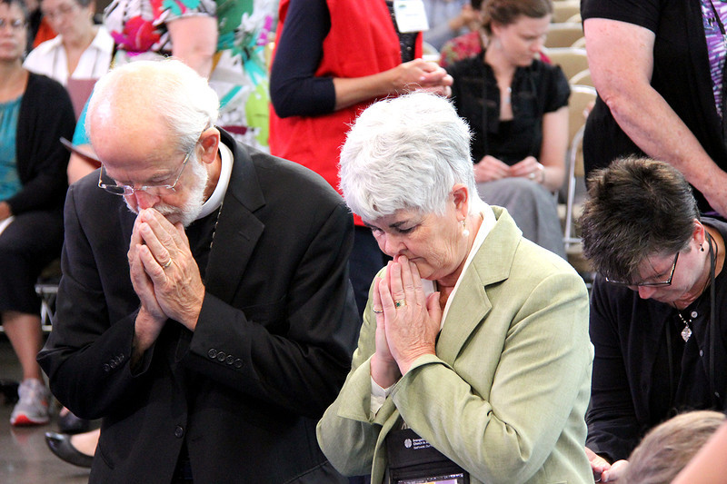 Presiding Bishop Mark Hanson and his wife, Mrs. Ione Hanson, kneel in prayer by the cross during worship.