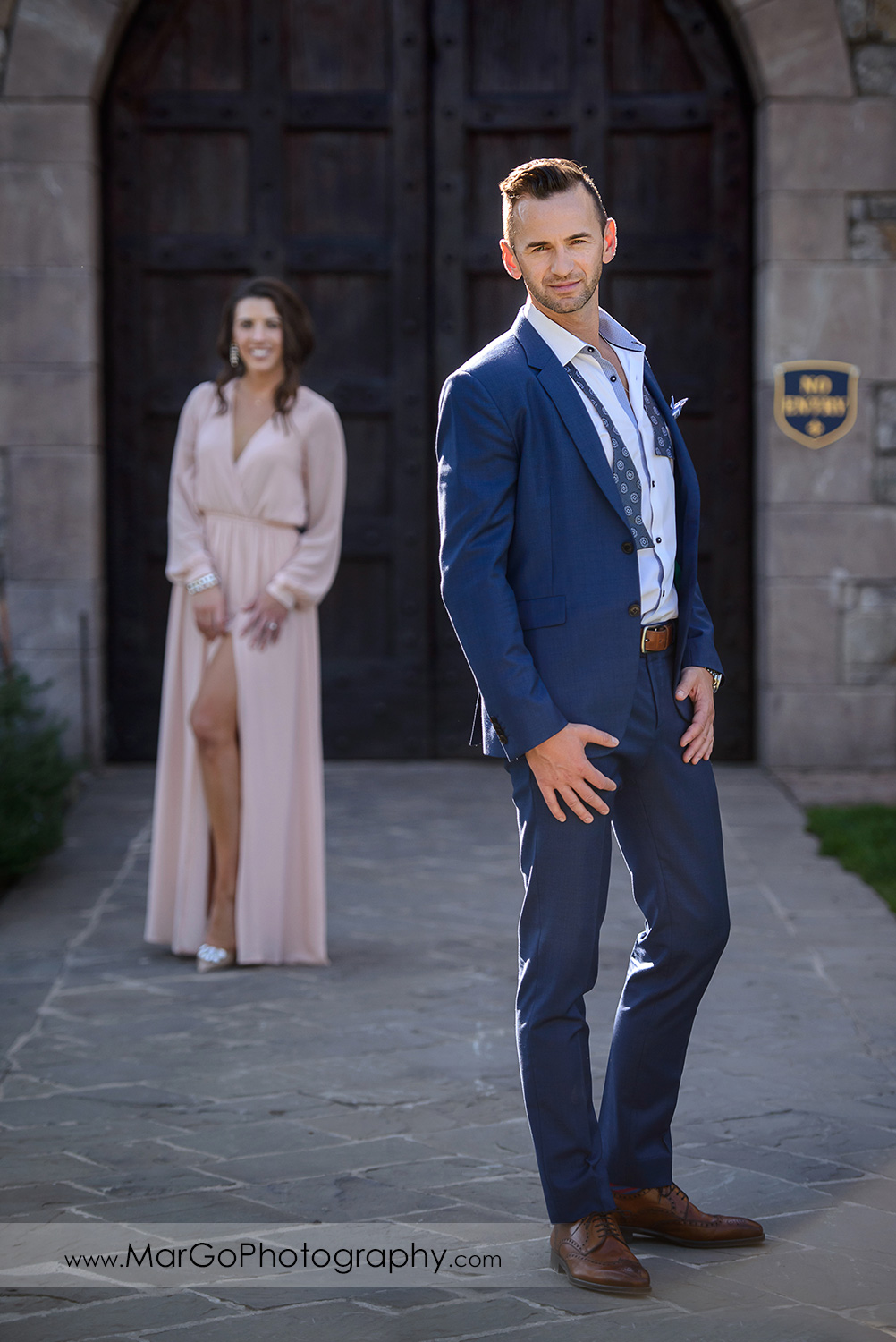 full body portrait of man in blue suit standing in front of woman in pink dress during Napa Valley engagement session at Castello di Amorosa in Calistoga