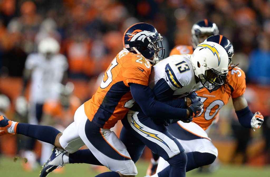 . San Diego Chargers wide receiver Keenan Allen (13) is taken down by Denver Broncos cornerback Quentin Jammer (23) in the fourth quarter. The Denver Broncos take on the San Diego Chargers at Sports Authority Field at Mile High in Denver on January 12, 2014. (Photo by Hyoung Chang/The Denver Post)