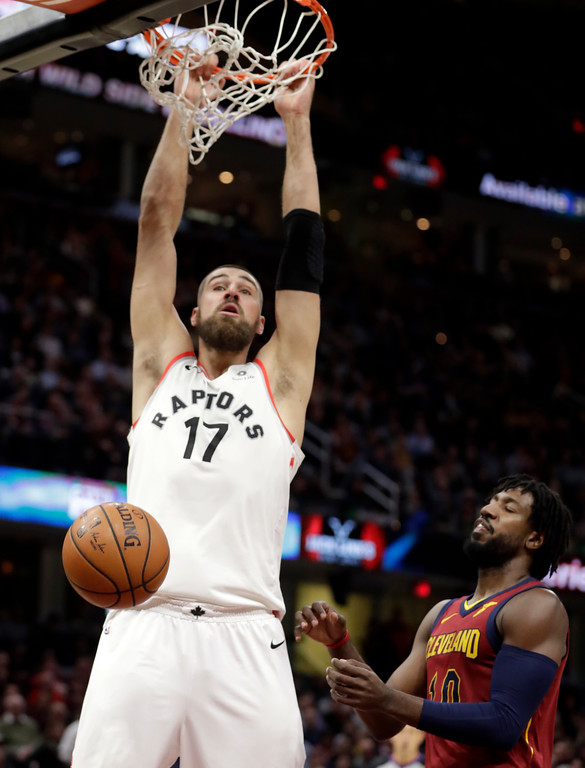 . Toronto Raptors\' Jonas Valanciunas (17), from Lithuania, dunks the ball against Cleveland Cavaliers\' John Holland (10) in the first half of an NBA basketball game, Wednesday, March 21, 2018, in Cleveland. (AP Photo/Tony Dejak)