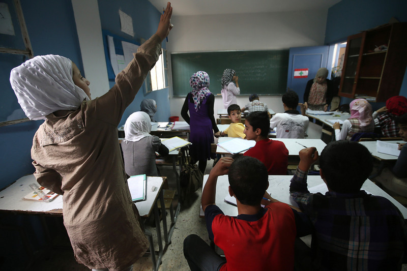 . In this picture taken on Thursday, May 29, 2014, a Syrian refugee student, left, raises her hand to answer a question in a classroom in a Lebanese public school where only Syrian students attend classes in the afternoon, in Kaitaa village in north Lebanon.  (AP Photo/Hussein Malla)