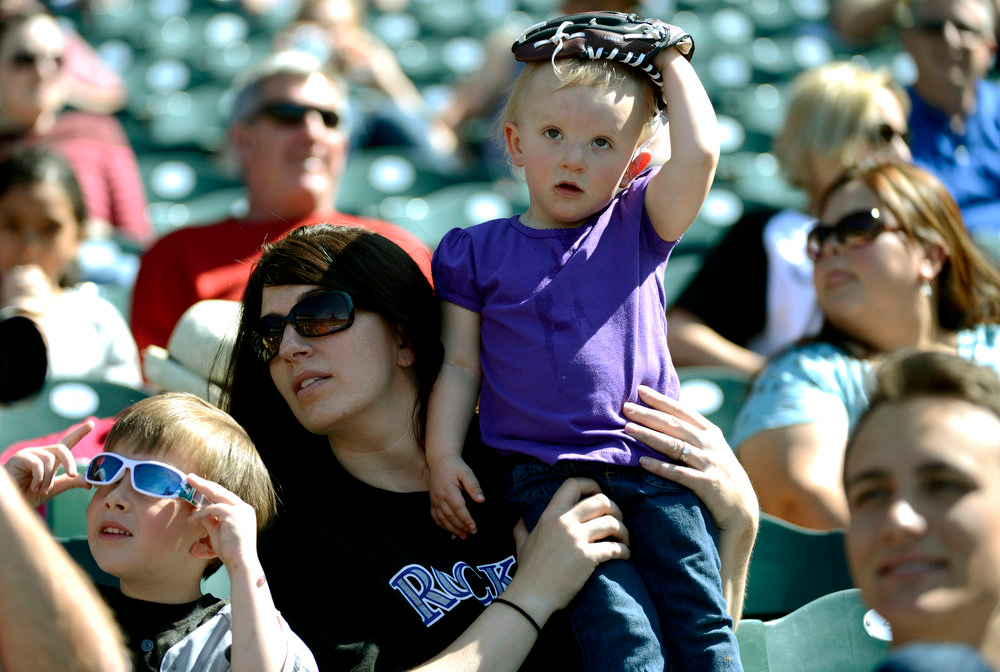 . Traci Montgomery holds on to her daughter Kellsie Montgomery 2-years-old as Grant Montgomery 4-years-old watches a ball sail to the outfield during the Rockies batting practice.  The Colorado Rockies hold an open practice for the fans April 4, 2013 at Coors Field. (Photo By John Leyba/The Denver Post)