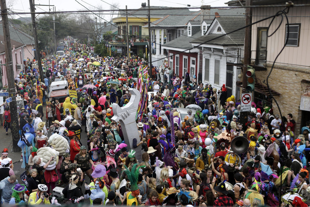 Description of . Revelers gather for the start of the Society of Saint Anne walking parade in the Bywater section of New Orleans during Mardi Gras day, Tuesday, Feb. 12, 2013.  Overcast skies and the threat of rain couldn't dampen the revelry of Mardi Gras as parades took to the streets, showering costumed merrymakers with trinkets of all kinds.  (AP Photo/Gerald Herbert)