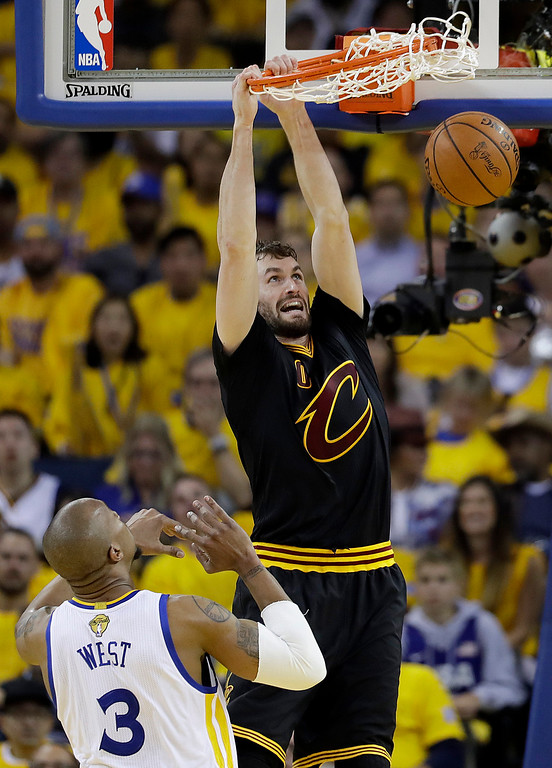 . Cleveland Cavaliers forward Kevin Love (0) dunks over Golden State Warriors forward David West (3) during the first half of Game 2 of basketball\'s NBA Finals in Oakland, Calif., Sunday, June 4, 2017. (AP Photo/Marcio Jose Sanchez)