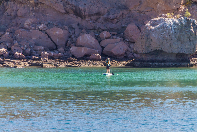 Woman doing stand up paddleboarding in sea near mountain - Mexico