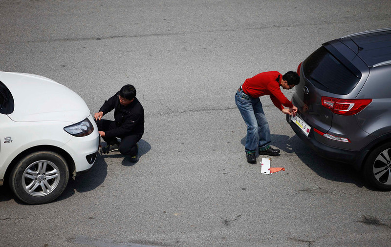 . South Korean employees working at the Kaesong Industrial Complex (KIC) change their license plates authorized by North Korea, to South Korean ones, upon arrival at the South\'s Customs, Immigration and Quarantine (CIQ) area, just south of the demilitarized zone separating the two Koreas, in Paju, north of Seoul, April 4, 2013. North Korea barred entry to a joint industrial complex it shares with the South for a second day on Thursday, the South Korean Unification Ministry said, but would allow 222 South Korean workers to leave the zone through the day.   REUTERS/Kim Hong-Ji