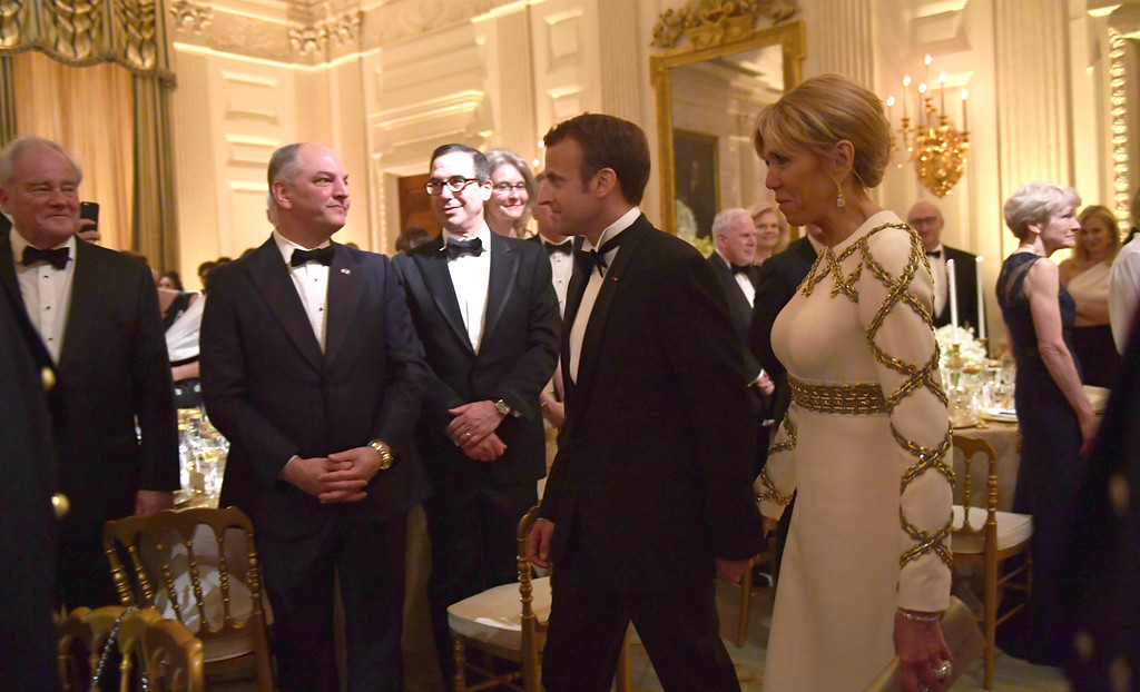 . French President Emmanuel Macron and his wife Brigette Macron walk into the State Dining Room to attend a State Dinner with President Donald Trump and first lady Melania Trump at the White House in Washington, Tuesday, April 24, 2018. (AP Photo/Susan Walsh)