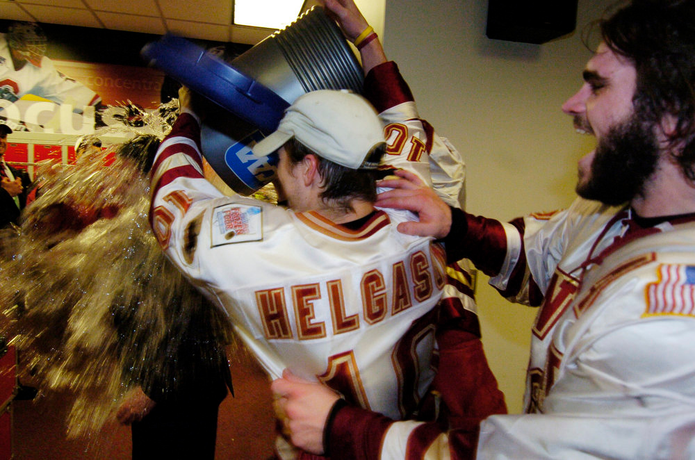. Denver University Pioneer Ryan Helgason, center, and Kevin Ulanski, douse head coach, George Gwozdecky in the locker room after defeating the North Dakota Sioux for the  the 2005 NCAA Division 1 Hockey Championship game at the Schottenstein Center in Columbus, Ohio Saturday evening. THE DENVER POST/ ANDY CROSS