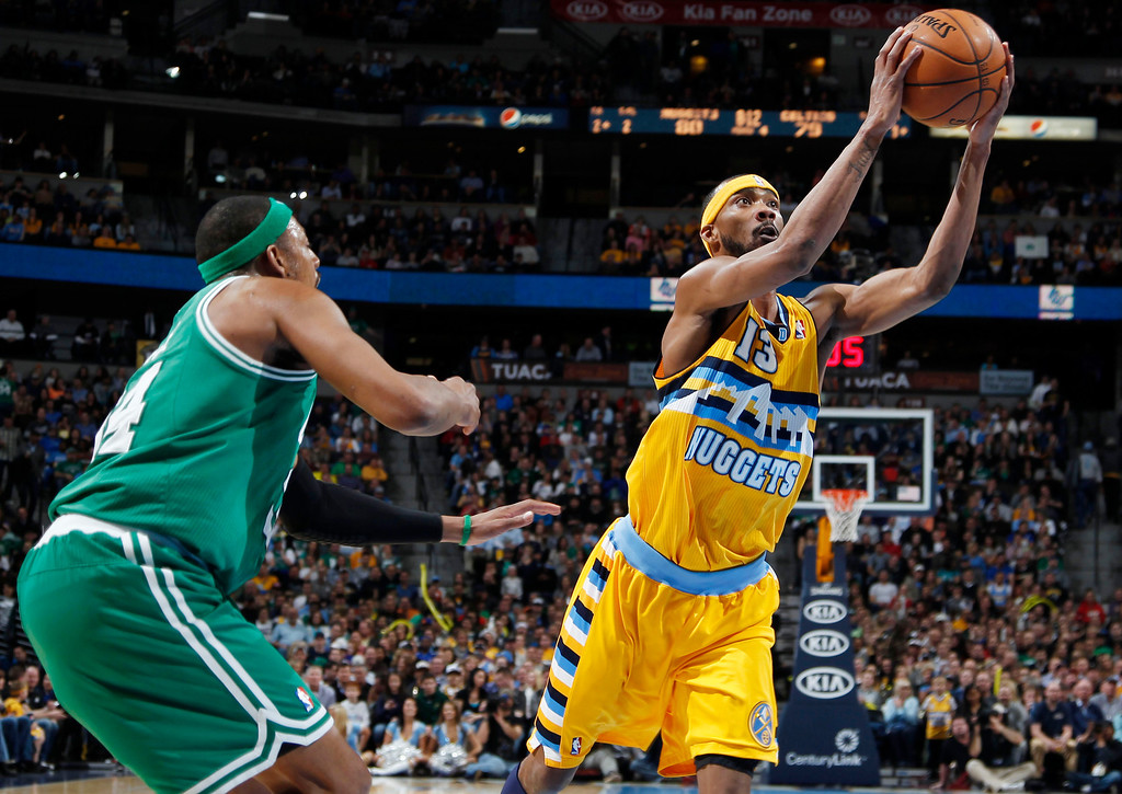 . Denver Nuggets forward Corey Brewer, right, slips past Boston Celtics forward Paul Pierce for a shot  in the fourth quarter of the Nuggets\' 97-90 victory in an NBA basketball game in Denver on Tuesday, Feb. 19, 2013. (AP Photo/David Zalubowski)
