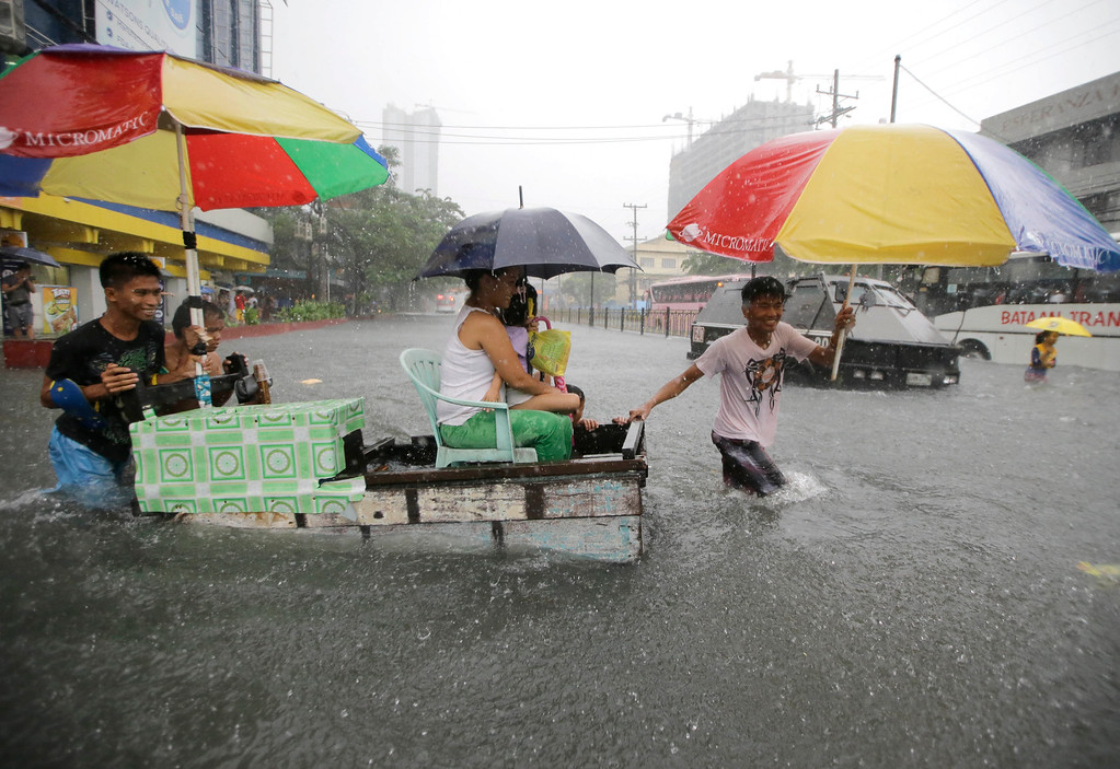 . Commuters cross a flooded street on a wooded cart after heavy monsoon rains spawned by tropical storm Fung-Wong flooded Manila and most parts of  the metropolis Friday, Sept 19, 2014 in the Philippines. (AP Photo/Bullit Marquez)