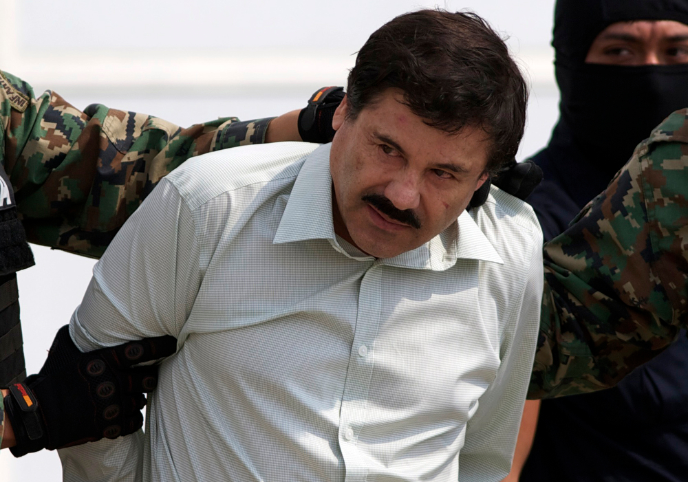 """. Joaquin \""""El Chapo\"""" Guzman is escorted to a helicopter in handcuffs by Mexican navy marines at a navy hanger in Mexico City, Saturday, Feb. 22, 2014. A senior U.S. law enforcement official said Saturday, that Guzman, the head of Mexicoís Sinaloa Cartel, was captured alive overnight in the beach resort town of Mazatlan. Guzman faces multiple federal drug trafficking indictments in the U.S. and is on the Drug Enforcement Administrationís most-wanted list. (AP Photo/Eduardo Verdugo)"""