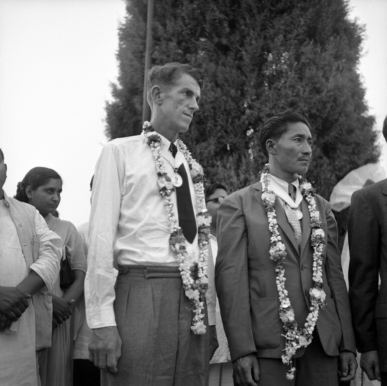 . Edmund Percival Hillary, 34, left, and Sherpa Tenzing Norgay, the 39-year-old Sherpa Sirdar, who reached the 29,002-feet summit of Mount Everest stand with garlands about their shoulders, wearing the specially struck gold medals with which they were presented by Dr. Rajendra Prasad, the Indian President, unseen, in New Delhi, India on June 29, 1953. They made the summit on May 29th.  (AP Photo)