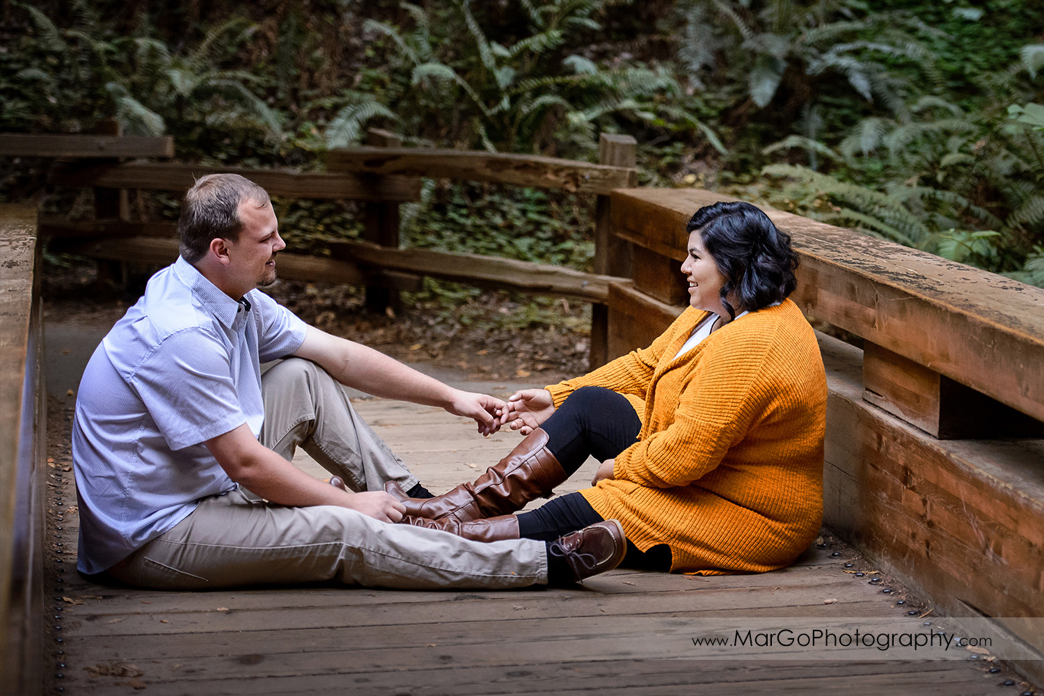 engaged couple sitting on the bridge at Muir Woods National Monument