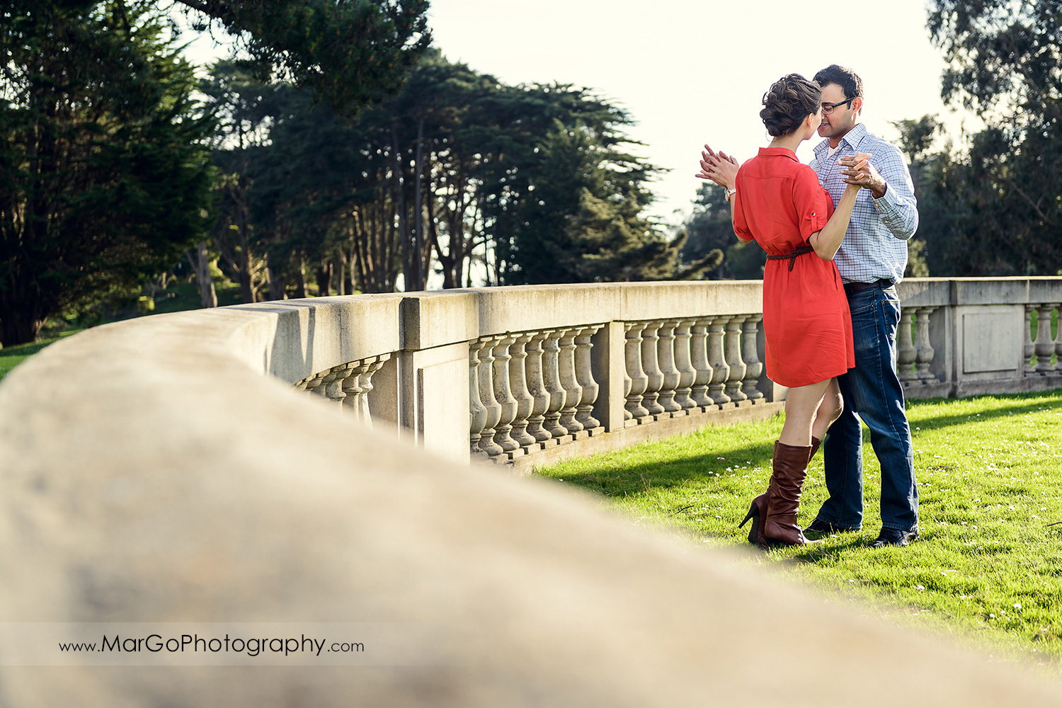 man in blue shirt and woman in red dress dancing on the grass patio during engagement session at San Francisco Legion of Honor