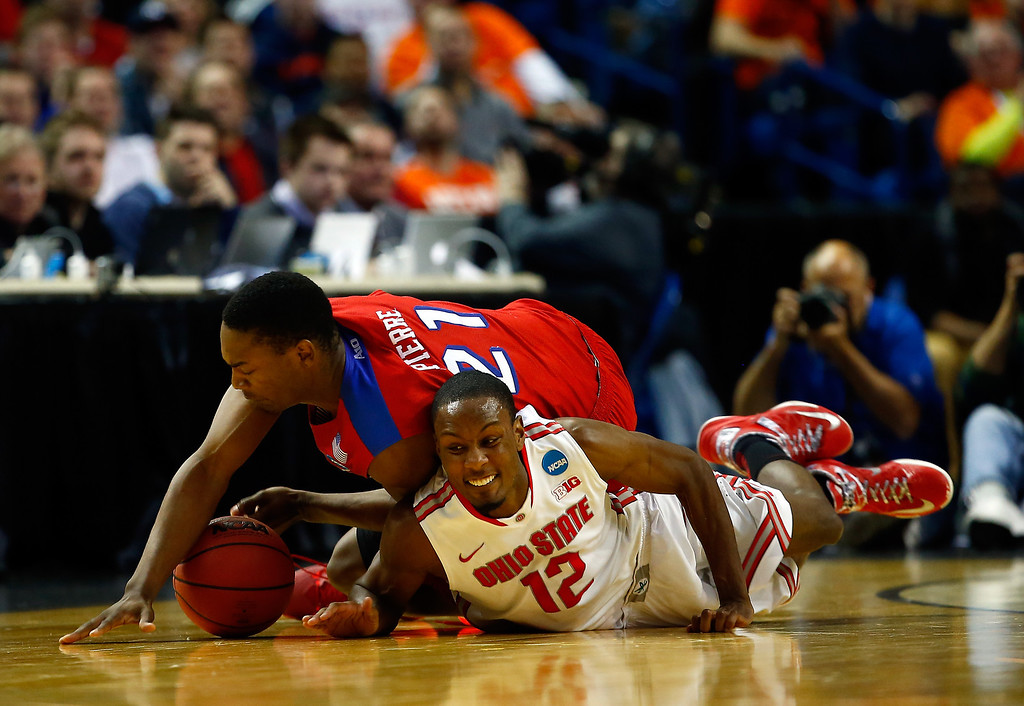 . Sam Thompson #12 of the Ohio State Buckeyes and Dyshawn Pierre #21 of the Dayton Flyers dive for a loose ball during the second round of the 2014 NCAA Men\'s Basketball Tournament at the First Niagara Center on March 20, 2014 in Buffalo, New York.  (Photo by Jared Wickerham/Getty Images)