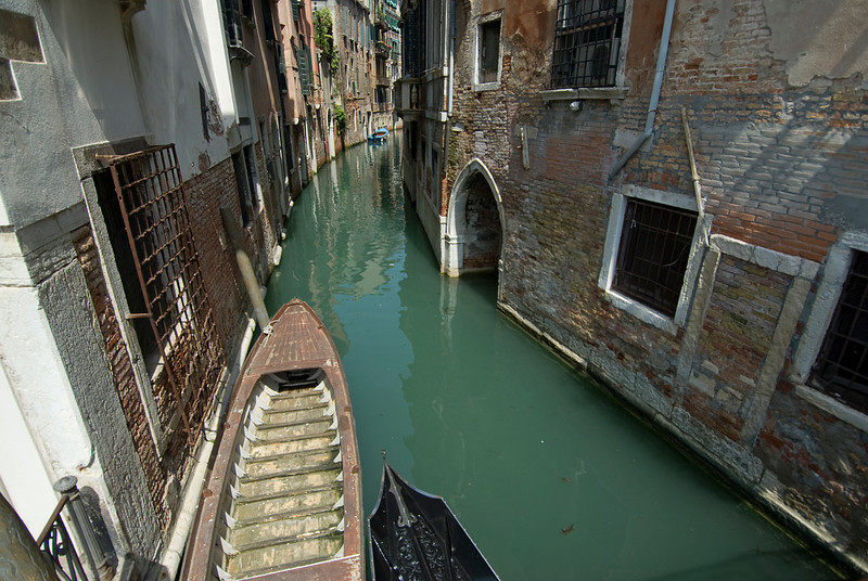 Gondola cruising a narrow canal in Venice, Italy