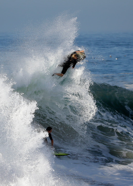 . A bogie boarder and a surfer ride a wave at the wedge, on Wednesday, Aug. 27, 2014 in Newport Beach, Calif. Beach goers experienced much higher than normal surf, brought on by Hurricane Marie spinning off the coast of Mexico. (AP Photo/Chris Carlson)