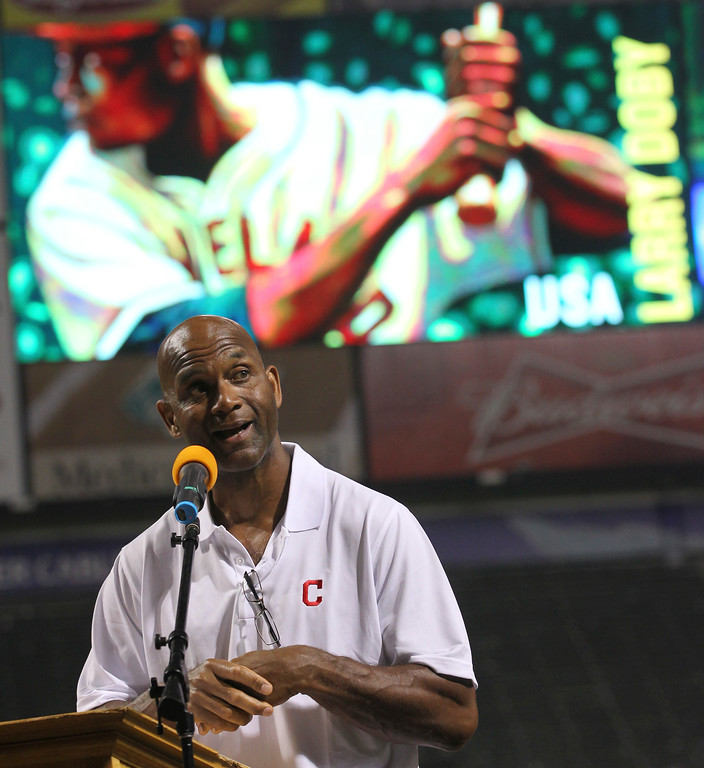. Larry Doby Jr. talks about his father, former Cleveland Indians\' Larry Doby, as the Cleveland Indians celebrate the 65th anniversary of Doby\'s integration into the American League, Friday, July 6, 2012, in Cleveland. Behind Doby Jr. on the screen is The Doby Stamp. The USPS will dedicate a stamp to Larry Doby on July 21st. The Indians played the Tampa Bay Rays in a baseball game. (AP Photo/Tony Dejak)