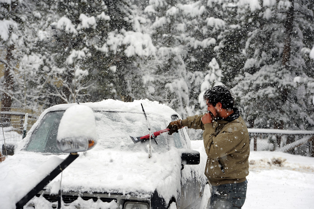 . Keith Facchin, of Nederland, CO blows on his hands to keep them warm as he clears snow off of his car while getting ready to head out to work on May 1, 2013.  Over 6 inches of snow has already fallen in Nederland, CO and forecasts call for snow through out the day on May 1, 2013.   (Photo by Helen H. Richardson/The Denver Post)