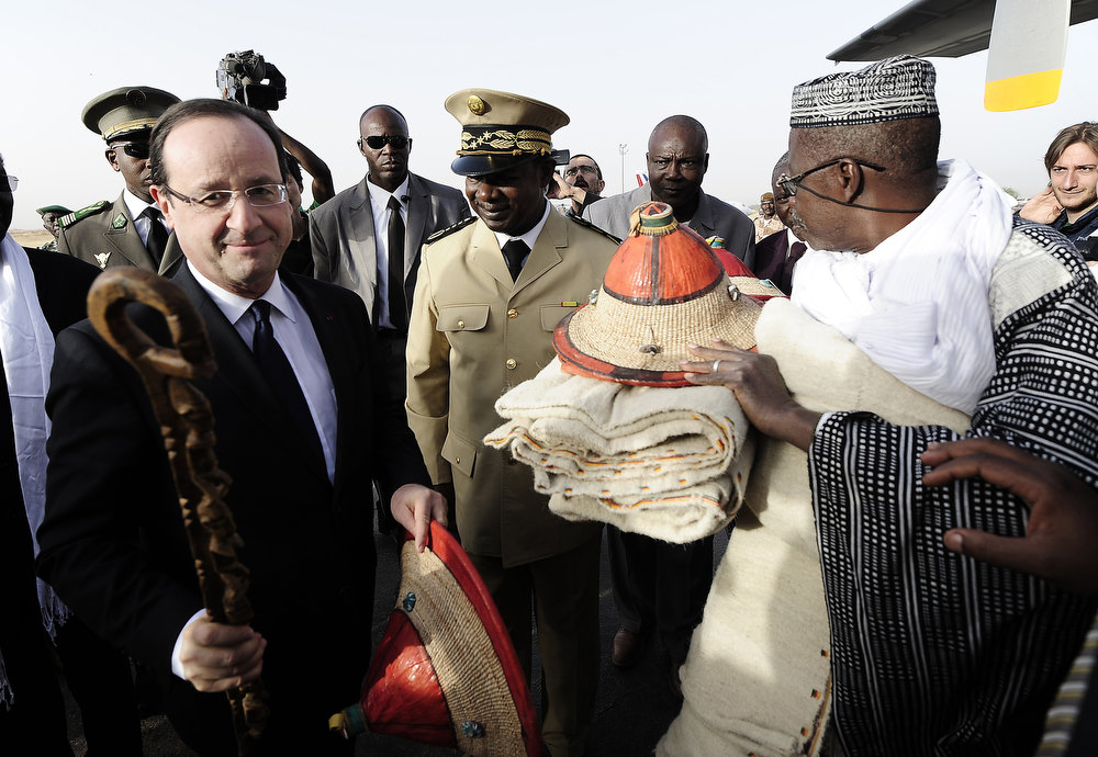 Description of . France\'s President Francois Hollande (L) receives presents upon his arrival at Sevare, near Mopti, on February 2, 2013. President Francois Hollande visits Mali as French-led troops work to secure the last Islamist stronghold in the north after a lightning offensive against the extremists. Hollande will head to Timbucku and Bamako. PASCAL GUYOT/AFP/Getty Images
