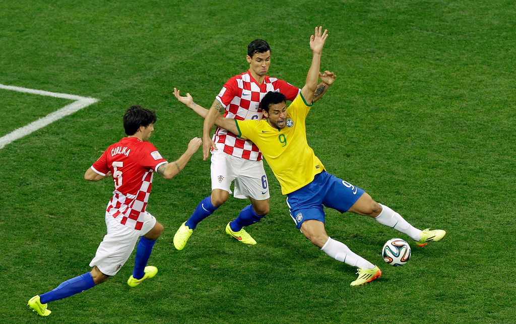 . Brazil\'s Fred, right, falls after making contact with Croatia\'s Dejan Lovren during the group A World Cup soccer match between Brazil and Croatia, the opening game of the tournament, in the Itaquerao Stadium in Sao Paulo, Brazil, Thursday, June 12, 2014. At left is Croatia\'s Vedran Corluka. (AP Photo/Thanassis Stavrakis)