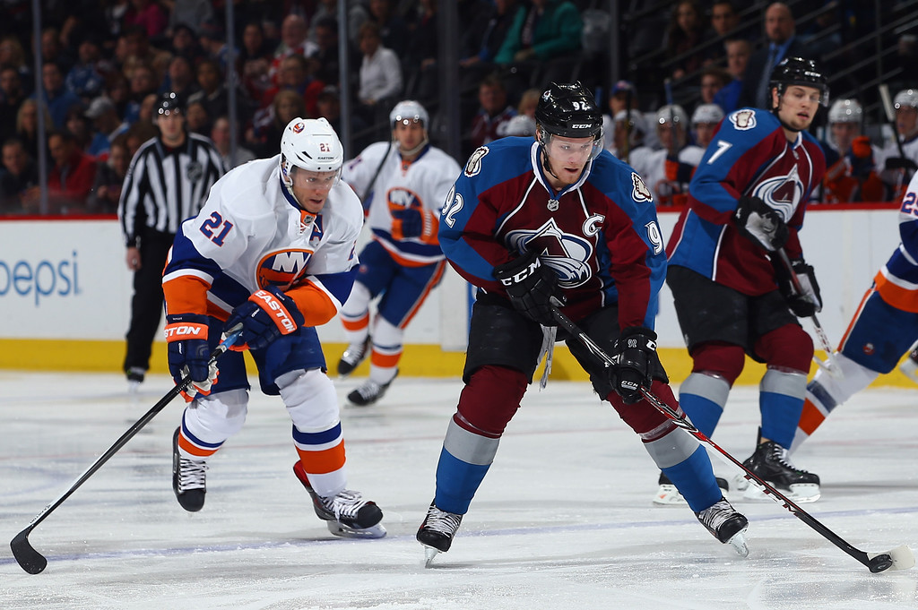 . DENVER, CO - JANUARY 10:  Gabriel Landeskog #92 of the Colorado Avalanche controls the puck against Kyle Okposo #21 of the New York Islandersat Pepsi Center on January 10, 2014 in Denver, Colorado.  (Photo by Doug Pensinger/Getty Images)
