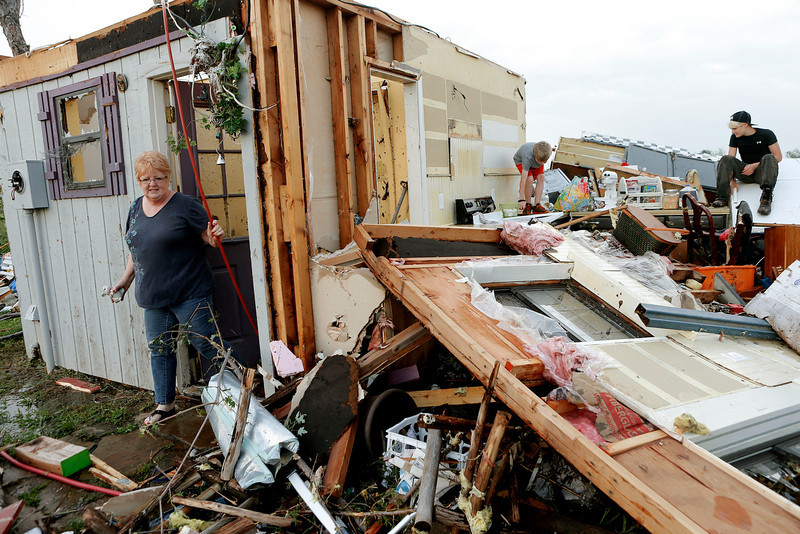 . Marlena Hodson walks out of her home as her grandsons, Campbell Miller, 10, and Dillon Miller, 13, at right, help her sort through belongings after a tornado damaged her home Carney Okla., on Sunday, May 19, 2013. Hodson and her family left the home to escape the tornado. (AP Photo/The Oklahoman, Bryan Terry)