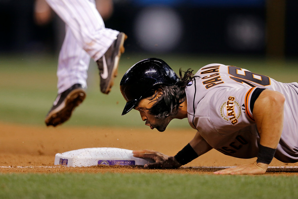 . San Francisco Giants\' Angel Pagan dives back to third after advancing from first on a Joe Panik double against the Colorado Rockies during the seventh inning of a baseball game Tuesday, Sept. 2, 2014, in Denver. (AP Photo/Jack Dempsey)