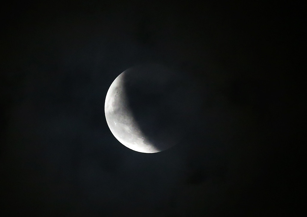 ". The Earth\'s shadow slowly passes by the moon during a total lunar eclipse on Wednesday, Oct. 8, 2014 from Quezon city, north of Manila, Philippines. Wednesday\'s eclipse was the second in a series of four total lunar eclipses that occur in six-month intervals and known as a ""lunar tetrad.\"" (AP Photo/Aaron Favila)"